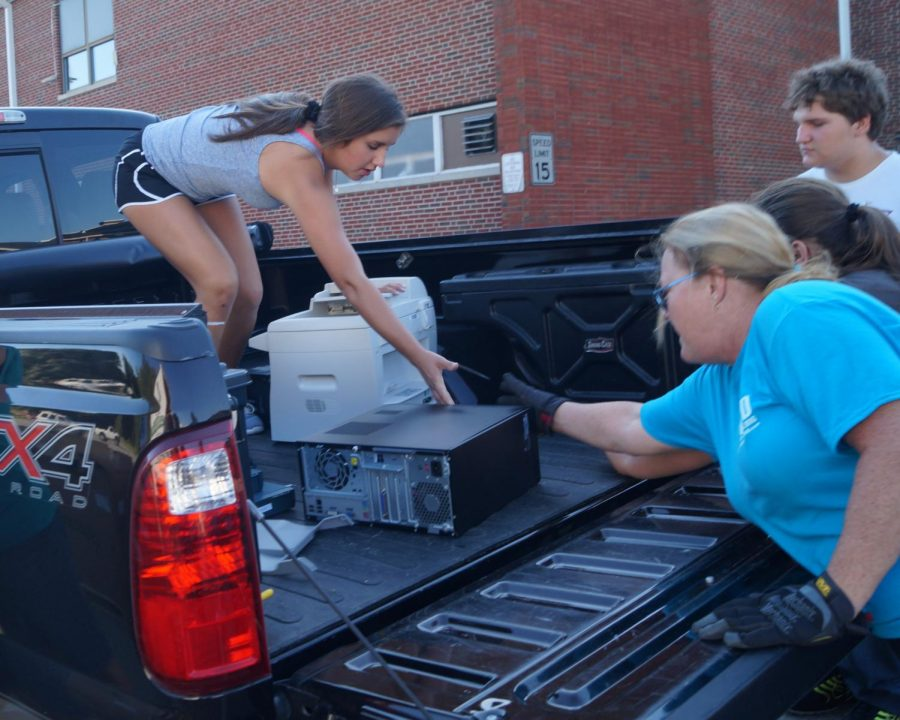 Ryn Petrowske helps to unload a vehicle at the e-cycle drive Oct. 6.