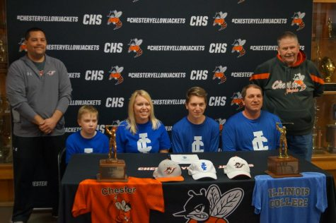 Jarrett James, flanked by his family and coaches, signs a letter of intent to play golf at Illinois College.