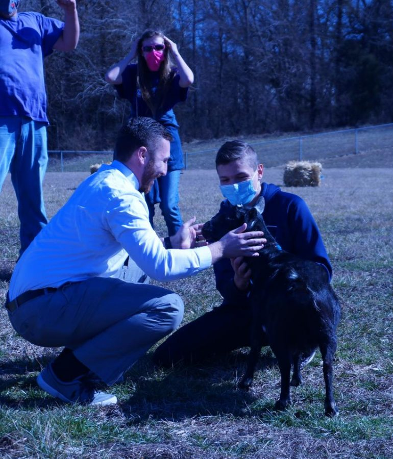 Mr. Cowan gets ready to kiss the goat as FFA President Blake Huffman looks on.