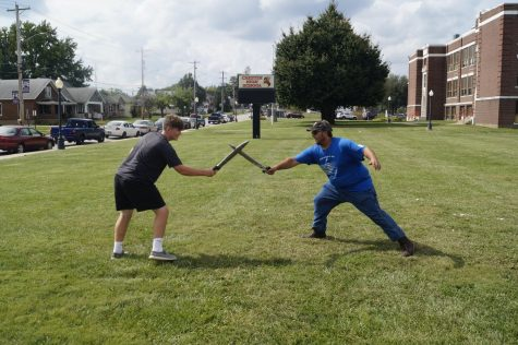 Kayden Freytag and Jerald Copple sword fight during the Feast of Ste. Jacquette.